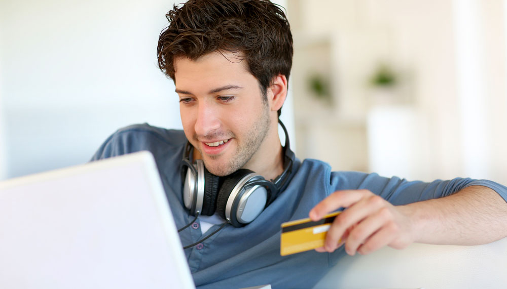 Young man buying a new home online with laptop and credit card in his hand
