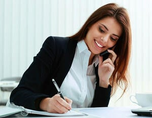 Smiling Female Online Sales Consultant talking on the phone